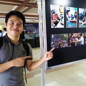 MCCID Photography winner poses in front of his works.